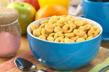A bowl full of honey flavored cereal loops, yogurt in glass, fresh fruits, orange juice and coffee (Selective Focus, Focus on the cereal loop in the middle of the bowl)