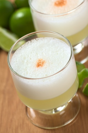 Peruvian cocktail called Pisco Sour made of Pisco (Peruvian grape schnaps), lime juice, syrup, egg white, and some angostura (bitter fluid) drops on top (Selective Focus, Focus on the middle of the angostura)