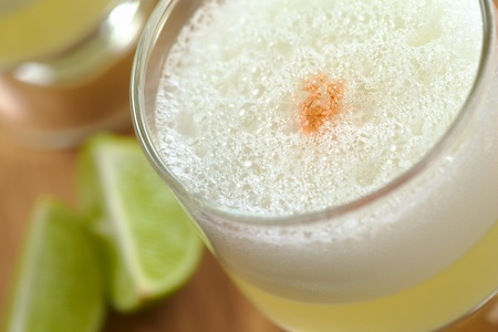 Peruvian cocktail called Pisco Sour made of Pisco (Peruvian grape schnaps), lime juice, syrup, egg white, and some angostura (bitter fluid) drops on top (Selective Focus, Focus on the front of the angostura) Imagens