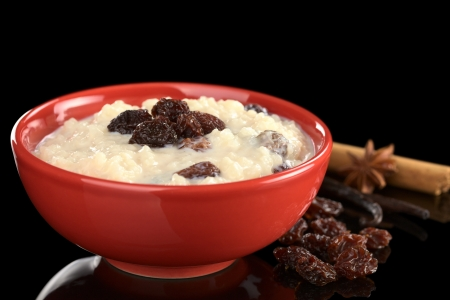 Rice pudding with raisins surrounded by raisins and spices such as vanilla, anise and cinnamon photographed on black (Selective Focus, Focus on the front of the raisins in the middle of the bowl) photo