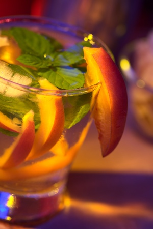 the height of a rim: Tamarillo cocktail (Very Shallow Depth of Field, Focus on the front edge of the mint leaf and the front of the tamarillo garnish at the height of the glass rim)