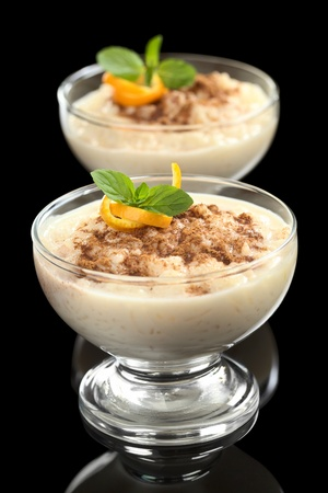 pudding: Delicious homemade rice pudding with cinnamon garnished with orange peel and mint leaf photographed on black (Selective Focus, Focus on the orange peel and the mint leaf on the first dessert) Stock Photo
