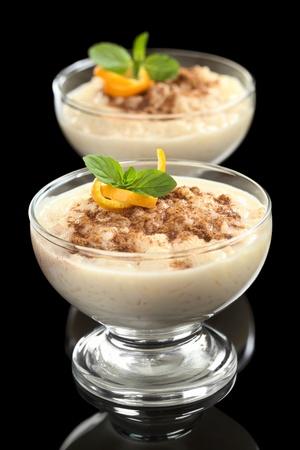 pudin: Pud�n de arroz hecha en casa deliciosa con canela adornada con piel de naranja y hojas de menta fotografiado en color negro (Enfoque, Enfoque en la piel de naranja y la hoja de menta en el postre primero) Foto de archivo