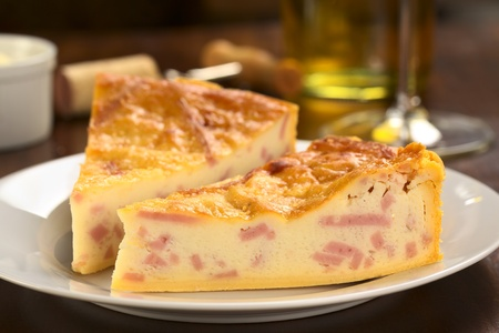Two slices of cheese and ham quiche with white wine in the back (Selective Focus, Focus on the front surface of the first slice) photo