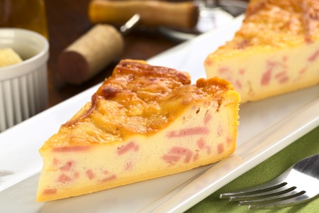 Two slices of cheese and ham quiche with corkscrew and cork in the back (Selective Focus, Focus on the middle of the first piece) photo