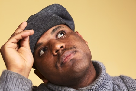 african descent: Portrait of a young man of African descent with a cap daydreaming (Selective Focus, Focus on the eyes)