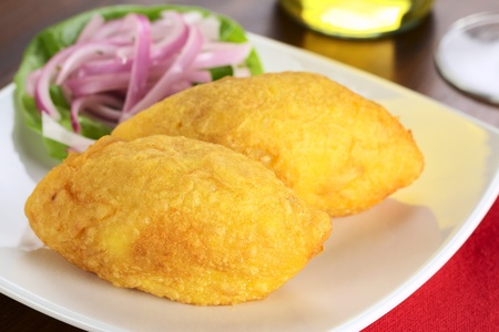 peru: Peruvian dish called Papa Rellena (Stuffed Potato) made of mashed potatoes and filled with meat (Selective Focus, Focus on right front part of the first papa rellena) Stock Photo