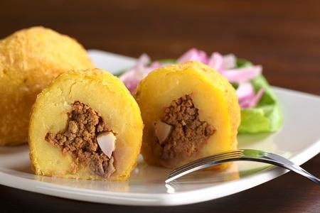 PURE: Plato peruano llamado Papa Rellena (patata rellena) hecha de puré de patata rellena de carne y huevo (Enfoque, Enfoque en la parte frontal de la media papa rellena)