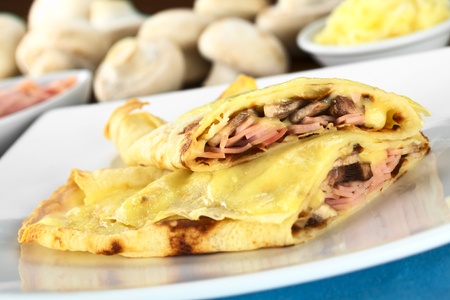 upper half: Rolled crepes filled with ham, cheese and white mushroom and baked with grated cheese on top (Selective Focus, Focus on the filling of the upper half crepe)
