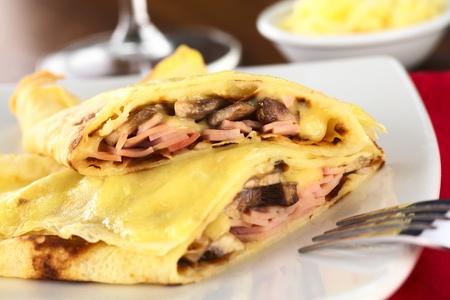crepas: Crepes rodadas relleno de jamón, queso y champiñones blancos y gratinado con queso rallado por encima (enfoque selectivo, foco en el llenado de la crepe mitad superior)