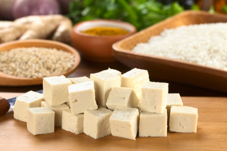 tofu: Raw tofu cut in dices on wooden board with rice and other raw ingredients in the back (Selective Focus, Focus on the front of the tofu)
