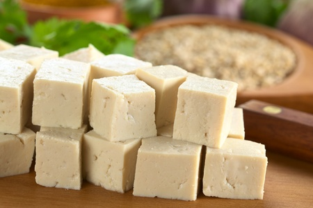 tofu: Raw tofu cut in dices on wooden board with other raw ingredients in the back (Selective Focus, Focus on the front of the tofu)