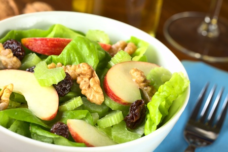 walnuts: Fresh home-made delicious Waldorf Salad consisting of lettuce, apple, celery, walnuts, raisins and mayonnaise (Selective Focus, Focus on the middle of the salad)