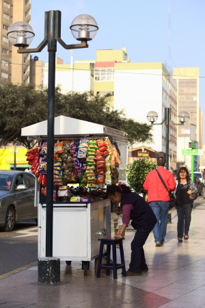 Lima, Peru - September 13, 2011: A street vendor in Miraflores, Lima selling sweets, small snacks and drinks. The unemployment rate in the Peruvian capital is very high, and many people earn their money selling snacks on the street. Some of these vendors  Stock Photo - 10752903