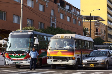 lima: Lima, Peru - September 13, 2011: Buses and a taxi standing at red light with a bus conductor standing on the street calling out for passengers. Buses and taxis are the main means of transportation in Lima. Most of the vehicles are old contributing to the  Editorial