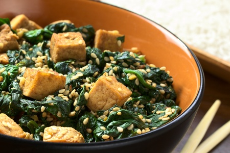 vegetarian cuisine: Tofu, spinach and sesame stir-fry fried with garlic and ginger, cooked rice in the back (Selective Focus, Focus on the front of the tofu one third into the bowl) Stock Photo