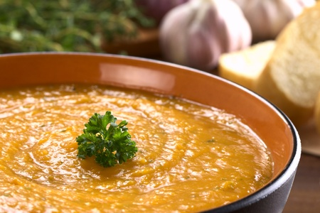 potato soup: Cream of sweet potato prepared with garlic, thyme and basil, garnished with fresh parsley (Selective Focus, Focus on the parsley) Stock Photo