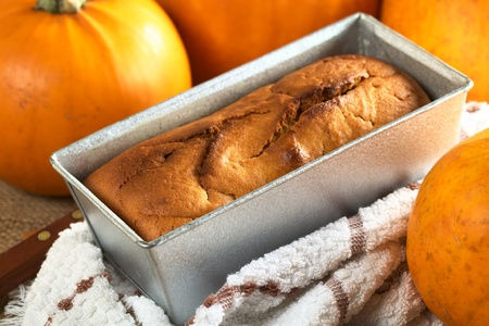 Fresh baked pumpkin bread in baking form with pumpkins around (Selective Focus, Focus one third into the bread on the left side) Stock Photo - 10909574