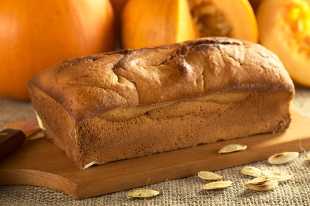 Fresh baked pumpkin bread on wooden board with pumpkin seeds and pumpkins (Selective Focus, Focus on the left front of the bread) photo