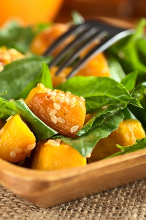 Baked pumpkin, spinach and sesame salad (Selective Focus, Focus on the pumpkin piece with many sesame seeds in the front) Stock Photo - 10909555