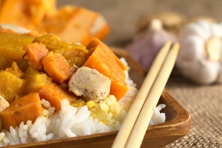 sweet course: Chicken, pumpkin and sweet potato curry served on rice in wooden plate with chopsticks (Selective Focus, Focus on the meat piece) Stock Photo