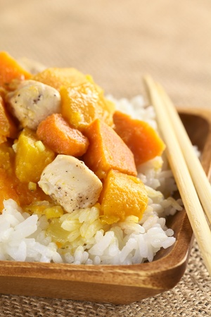 Chicken, pumpkin and sweet potato curry served on rice in wooden plate with chopsticks (Selective Focus, Focus on the meat and pumpkin pieces in the front) photo