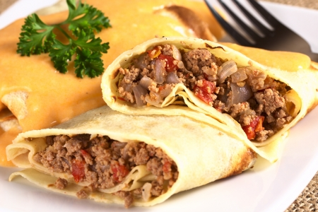 upper half: Hungarian-style crepe called Hortobagyi Husos Palacsinta (Crepe a la Hortobagy) filled with a mix of meat, tomato and onion amd served with sauce (Selective Focus, Focus on the stuffing in the upper half) Stock Photo
