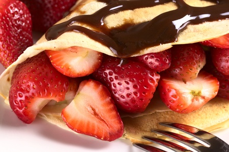 crepes: Crepe filled with fresh strawberries and chocolate sauce on top (Selective Focus, Focus on the strawberry cut on the left and the front of the two strawberries beside)