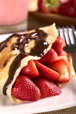 Crepe filled with fresh strawberries and chocolate sauce on top (Selective Focus, Focus on the strawberry in the front)