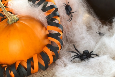 Halloween decoration consisting of pumpkin, plastic spider, artificial spider web and black-orange colored paper streamer (Selective Focus, Focus on the spider in the right bottom corner) photo