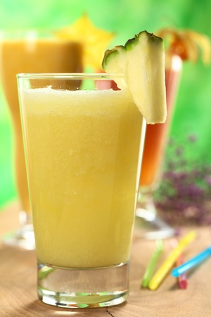 Fresh pineapple juice with papaya and mango juices in the back (Selective Focus, Focus on the front of the glass rim, and the front of the pineapple slice)