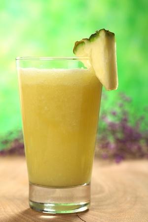 Jus d'ananas frais (au point sélective, Focus sur l'avant de la jante en verre, et l'avant de la tranche d'ananas)