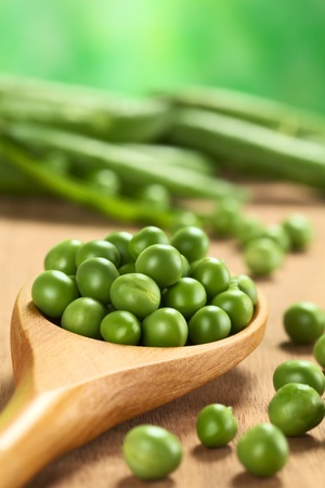 green pea: Fresh raw green pea (lat. Pisum Sativum) seeds on wooden spoon