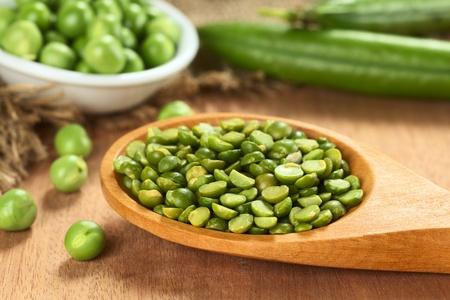 生バックで新鮮なグリーン ピースと木製のスプーンでエンドウ豆の分割 写真素材