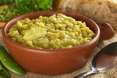 素朴なボウル (選択的なフォーカス ボールに 3 分の 1) のジャガイモとエンドウ豆の分割スープ