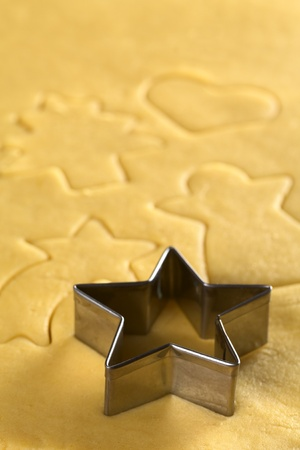 pastry cutter: Star-shaped cookie cutter and other Christmas shapes cut into dough (Selective Focus, Focus on the two front edges of the star-shaped cutter)