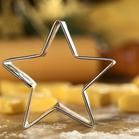 cookie cutter: Star-shaped cookie cutter with raw cookies and rolling pin in the back (Selective Focus, Focus on the front edge of the cutter)