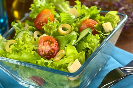 Fresh vegetable salad made of cherry tomato, cucumber, green olives and cheese photo
