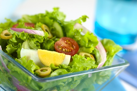 Fresh salad made of egg, lettuce, onion, tomato, cucumber and green olives  photo