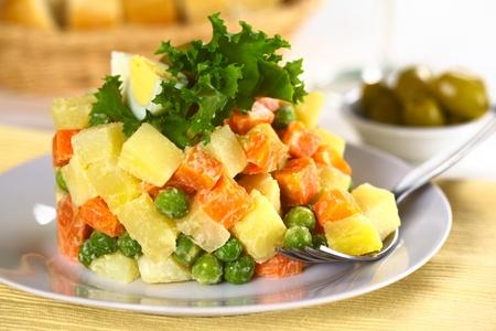 ensalada rusa: Ensalada Vegetariana de Rusia, también llamada Ensalada Olivier, hecha de papa, zanahoria y guisantes mezclados con mayonesa (Enfoque, Enfoque en las verduras en el tenedor y la comida en el mismo plano) Foto de archivo