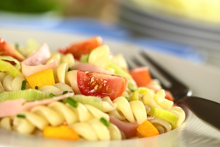 Pasta salad with leek, cherry tomato, yellow bell pepper and ham garnished with chives (Selective Focus, Focus on the tomato in the front) photo