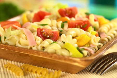 pasta salad: Pasta salad with leek, cherry tomato, yellow bell pepper and ham garnished with chives (Selective Focus, Focus on the tomato in the front)