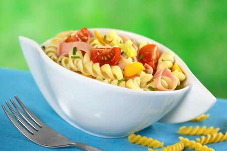 Pasta salad with leek, cherry tomato, yellow bell pepper and ham garnished with chives (Selective Focus, Focus on the tomato and the yellow bell pepper in the front) photo