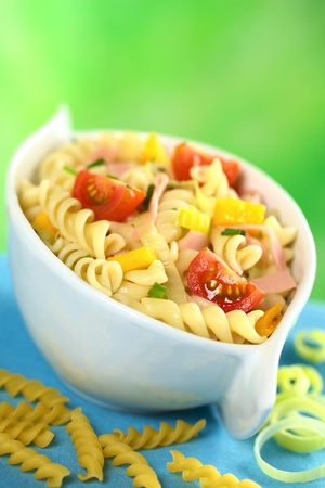 pasta salad: Pasta salad with leek, cherry tomato, yellow bell pepper and ham garnished with chives (Selective Focus, Focus on the tomato and the yellow bell pepper in the front)