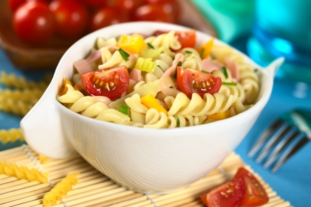 twist: Pasta salad with leek, cherry tomato, yellow bell pepper and ham garnished with chives (Selective Focus, Focus on the complete front part of the left tomato and the left side of the right tomato) Stock Photo