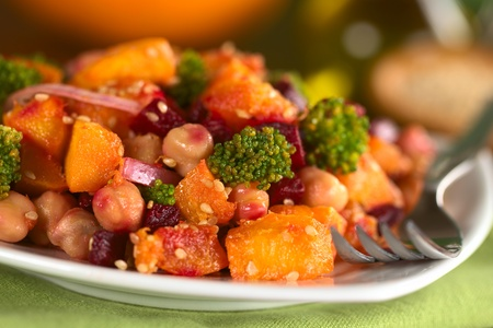 chickpea: Pumpkin, beetroot, broccoli and chickpea salad garnished with sesame seeds (Selective Focus, Focus on the broccoli floret in the front and the pumpkin piece left to it)