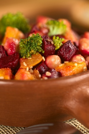 Pumpkin, beetroot, broccoli and chickpea salad garnished with sesame seeds (Selective Focus, Focus on the bigger broccoli floret in the front and the vegetables around it)  photo