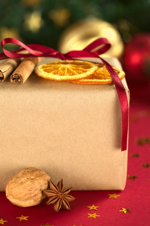 Christmas present decorated with dried orange slices and cinnamon (Selective Focus, Focus on the front of the orange slices and the cinnamon stick) Stock Photo - 11398022