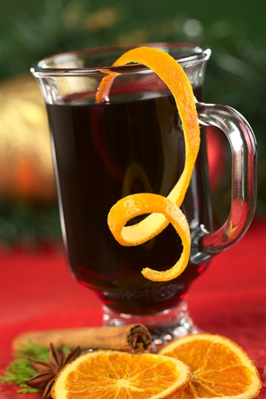 spiced: Hot spiced mulled wine garnished with orange peel (Selective Focus, Focus on the front rim of the glass and the orange peel at the rim)
