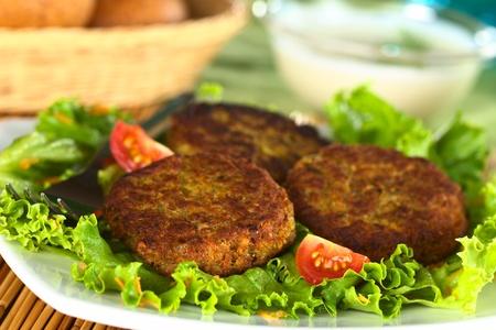 Végétarien hamburger aux lentilles en lentilles brunes et carottes râpées servi sur de la laitue (Mise au point sélective, Concentrez-vous sur le devant de hamburger d'abord sur la gauche)
